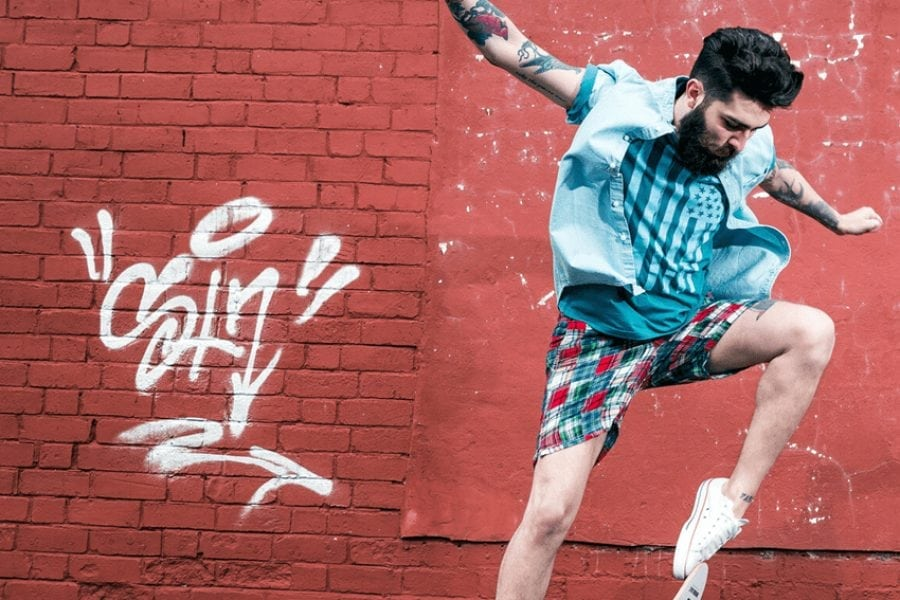 Man doing a skateboard trick in front of a wall with graffiti on it