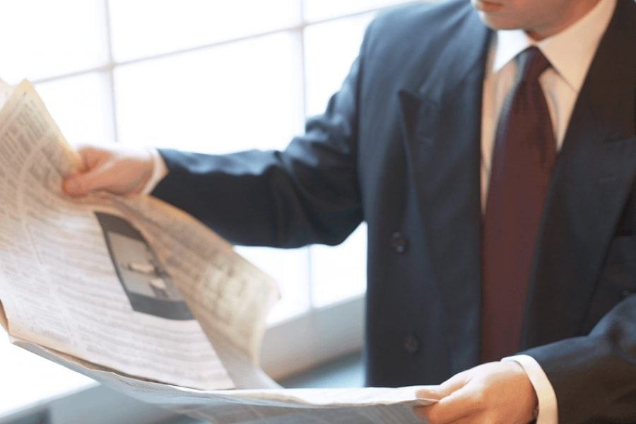 Man in suit reading a news paper