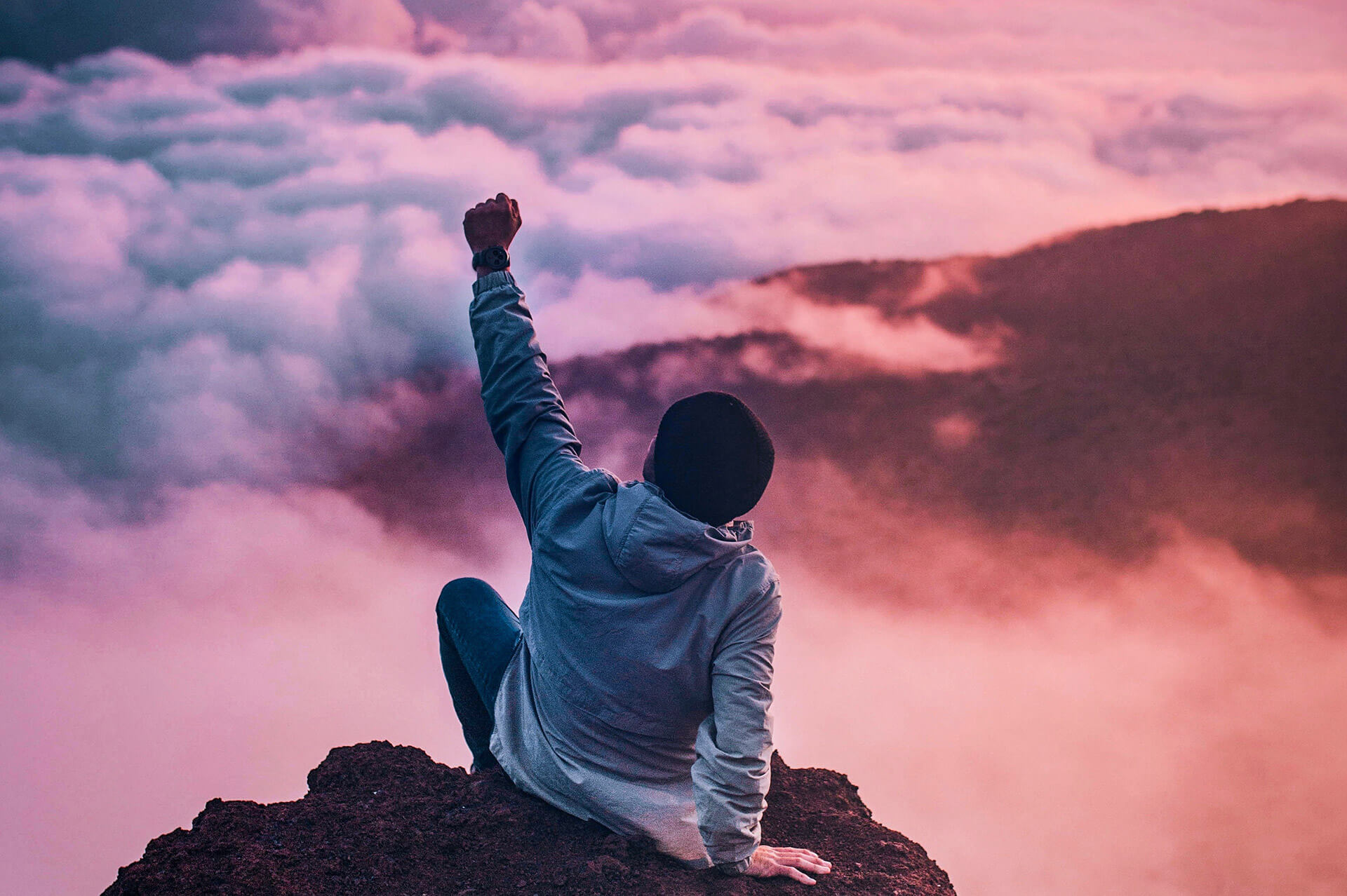Person at the top of mountain with fist in the air
