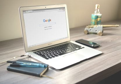 Google homepage on laptop on table