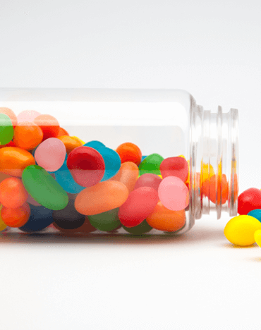 Colourful jelly beans spilling out of a jar