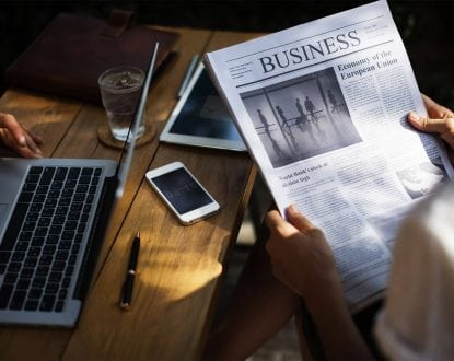 Person holding Business newspaper near grey laptop