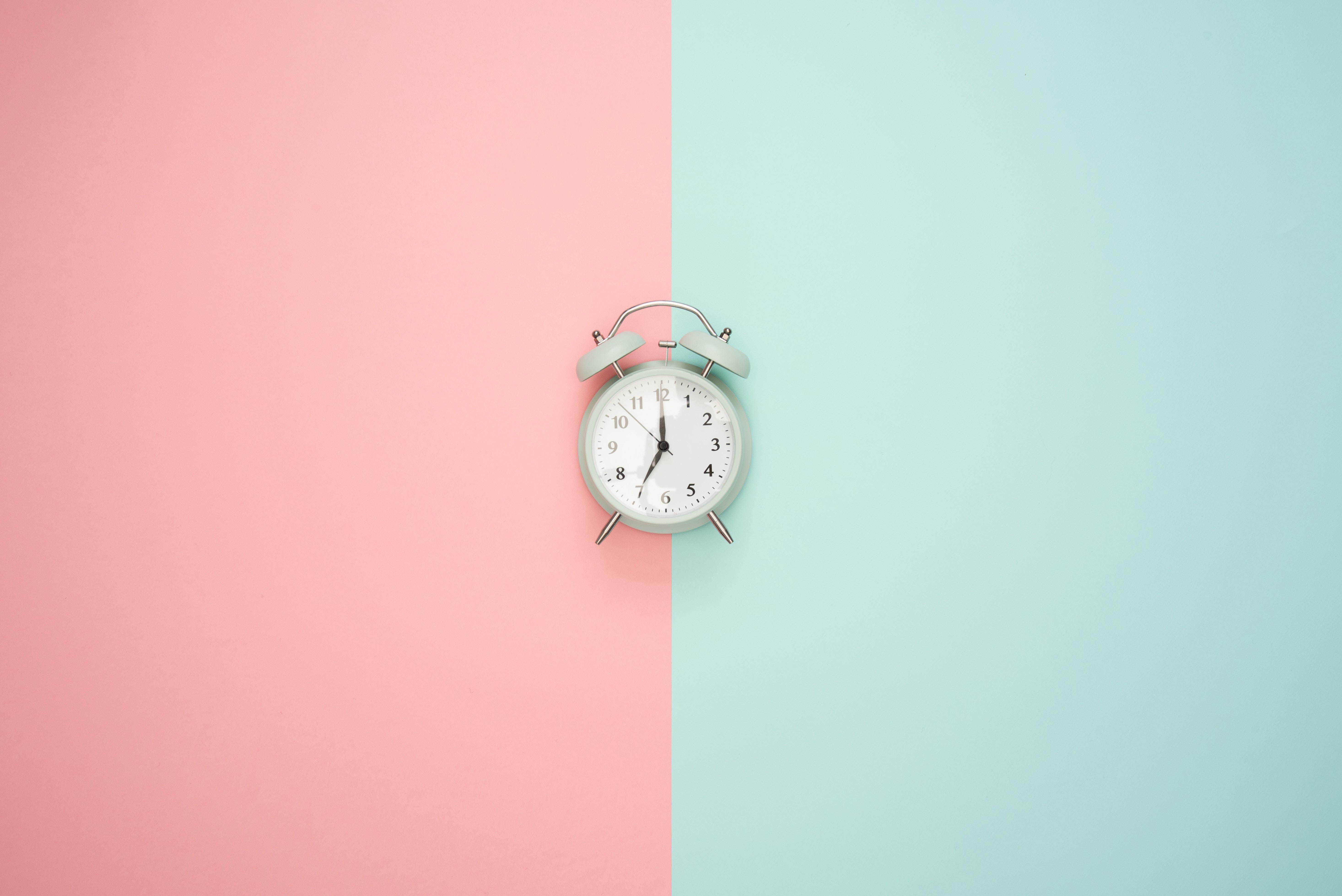 Alarm clock between light blue and light pink panels