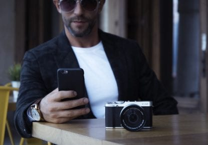 man wearing sunglasses, using smart phone, with camera atop table