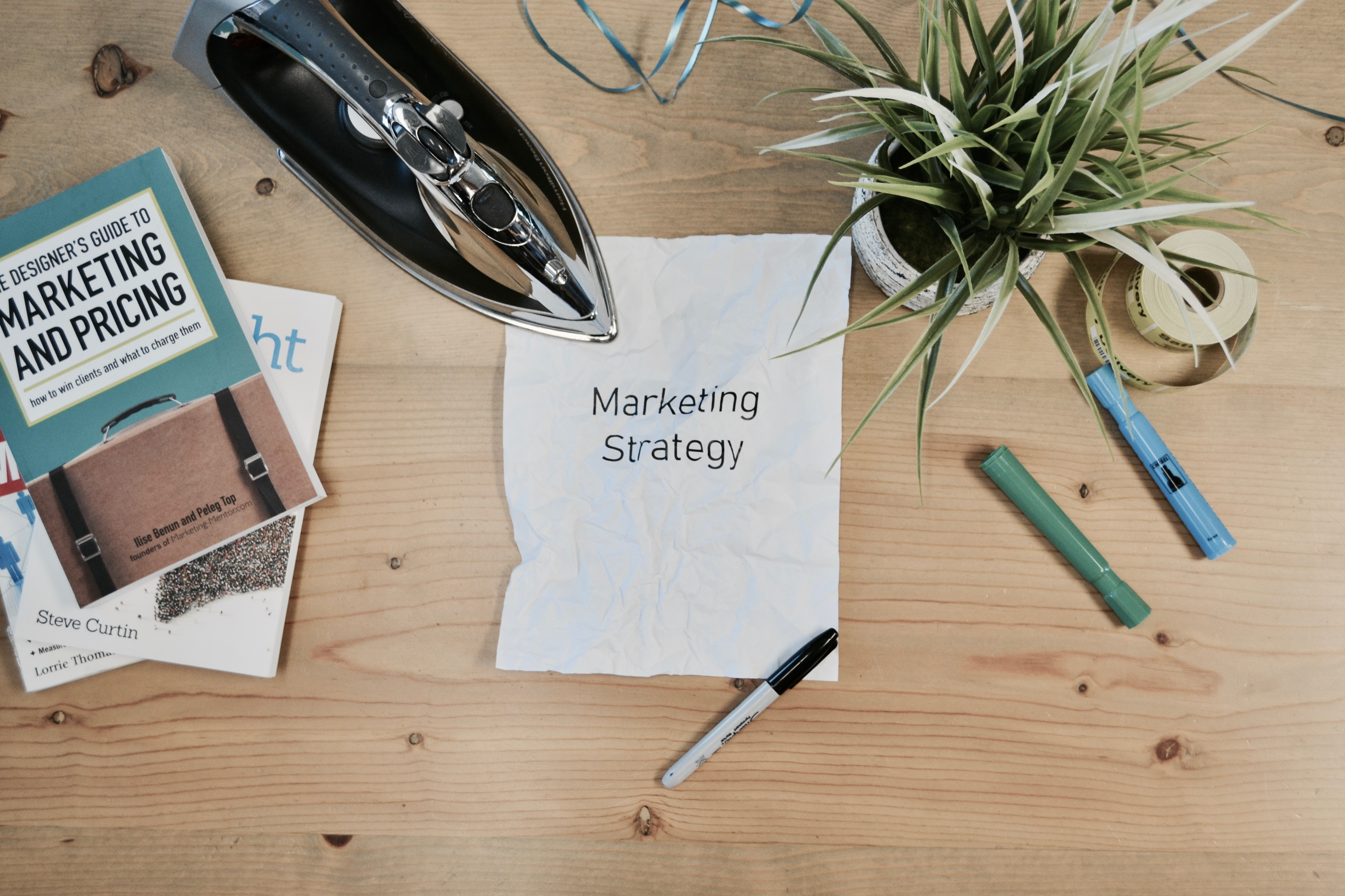 """A4 sheet reading """"marketing strategy"""", surround by assorted items, including a clothes iron and potted plant"""