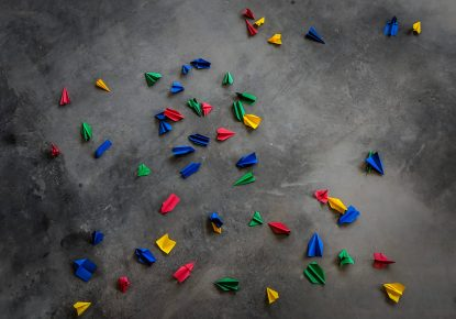 Paper aeroplanes in green, blue yellow and red, scattered across a dark stone floor