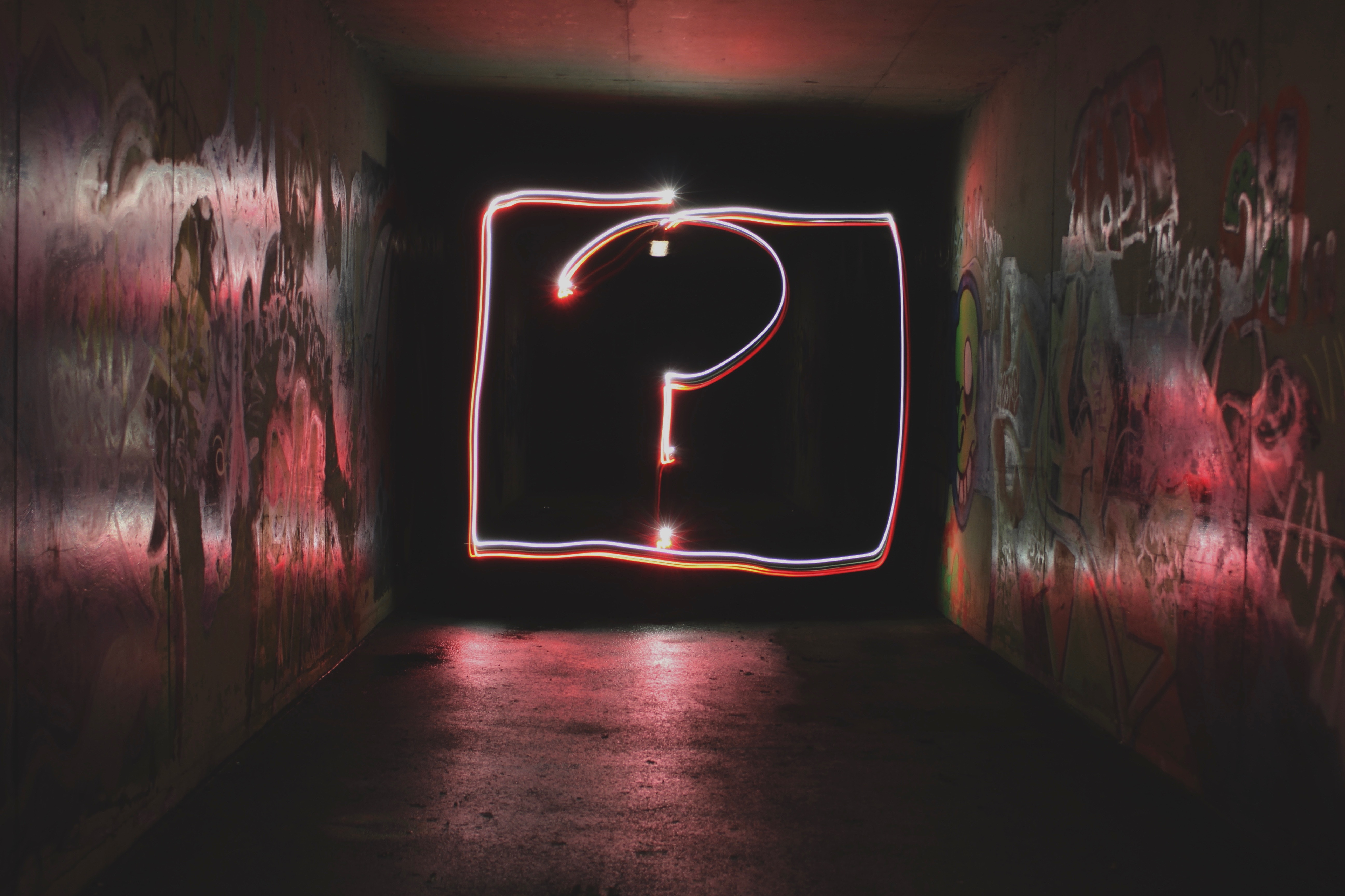 Neon lights in the shape of a question mark in a graffitied tunnel