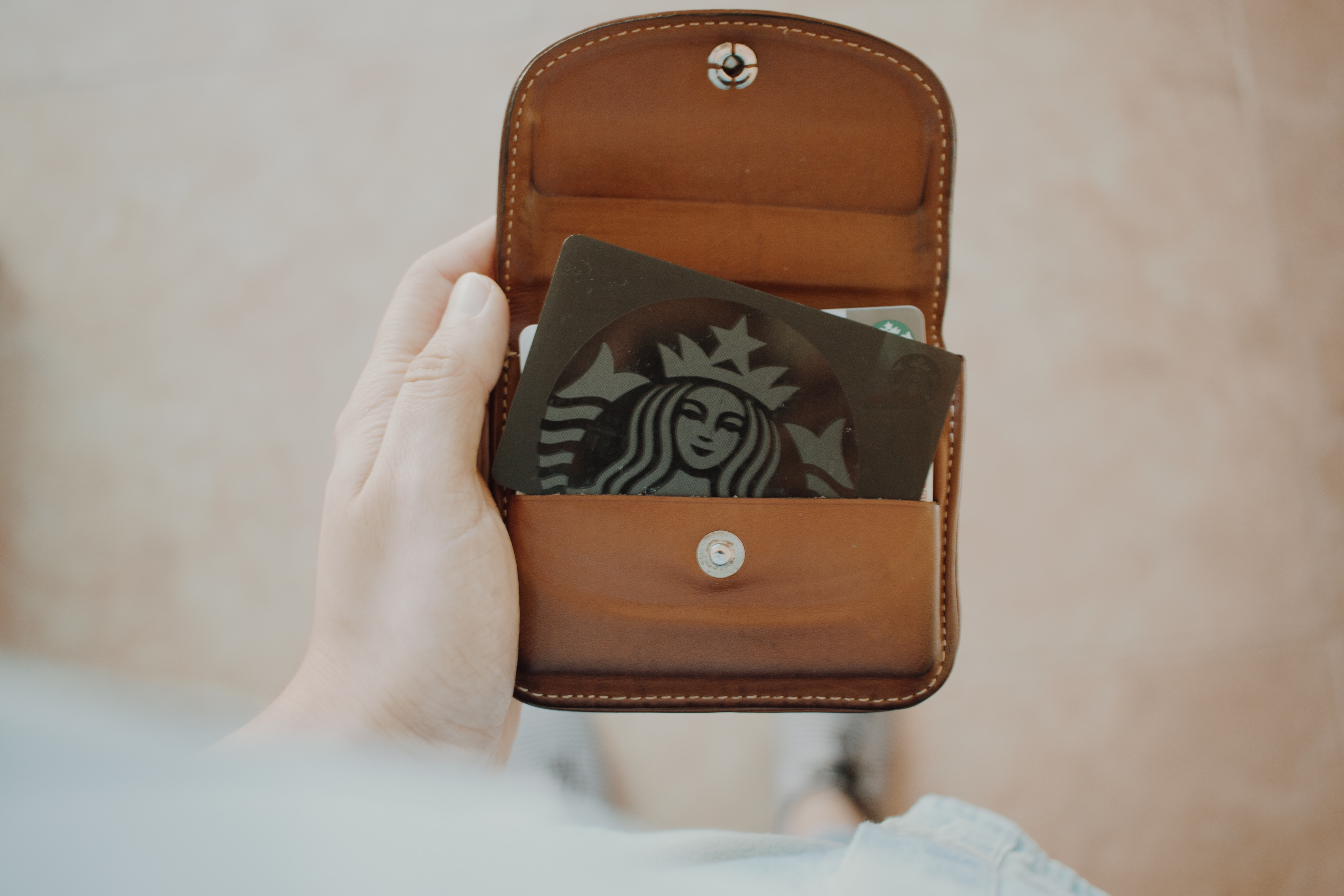 a starbucks loyalty card inside a brown leather purse