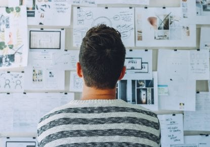 Man looking at wall of notes to get ideas