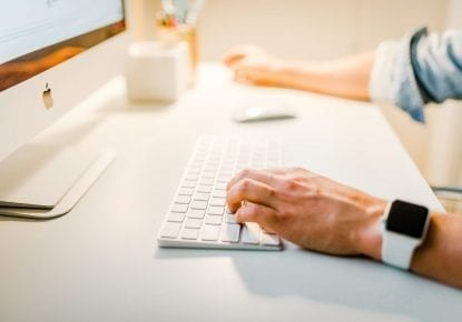 Person sits carrying out content audit on Apple computer
